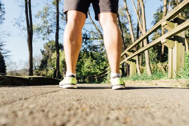 Widok z tyłu nóg i trampek biegacza na ścieżce w parku przeznaczonym do biegania z myślą o bieganiu z myślą o higienie osobistej