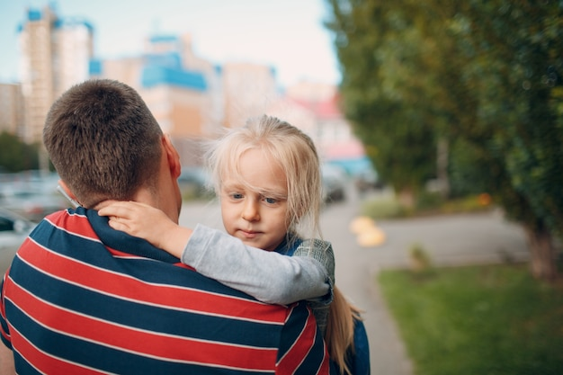 Widok z tyłu ojca idącego do przedszkola z córeczką.