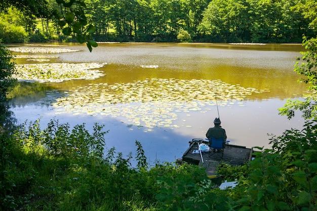 Widok z tyłu osoby grubej łowienie ryb na jeziorze w wiltshire w wielkiej brytanii we wczesnych godzinach porannych