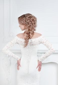 Widok z tyłu. panna młoda w sukni ślubnej stojąca przed lustrem