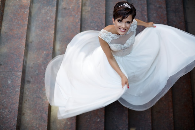 Widok z tyłu panny młodej w białej sukni ślubnej z krótkimi włosami, chowa się i uśmiecha, patrząc w kamerę.