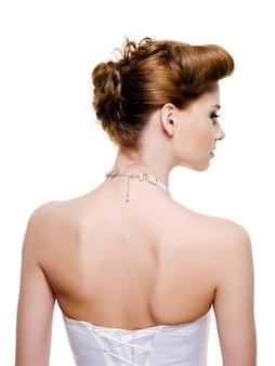 Widok z tyłu panny młodej z fryzury ślubnej mody na białym tle