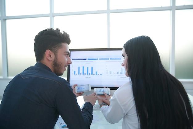 Widok z tyłu. para biznesowa omawiająca wykresy finansowe, siedząca przy biurku. ludzie i technologia