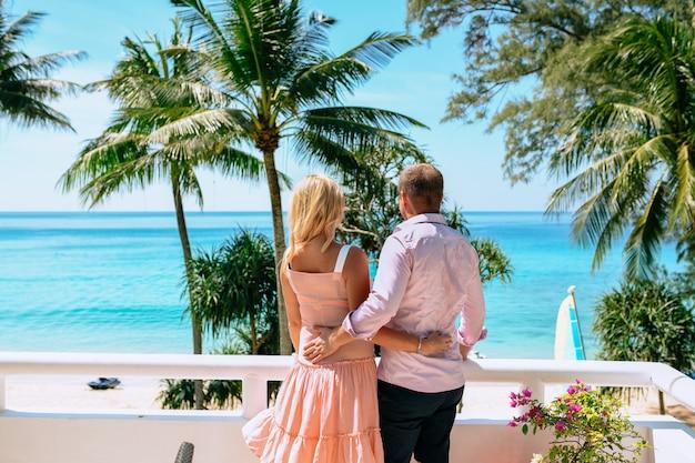 Widok z tyłu para przytulająca się na balkonie swojego hotelu podczas wakacji. morze i palmy