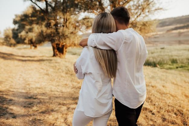 Widok z tyłu para przytulanie i spacery po trawie w parku.