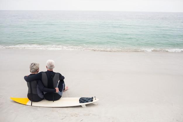 Widok z tyłu para siedzi na desce surfingowej