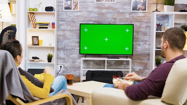 Widok z tyłu para siedzi na krześle rozmawiając przed telewizorem z zielonym ekranem, podczas gdy kot chodzi po pokoju.