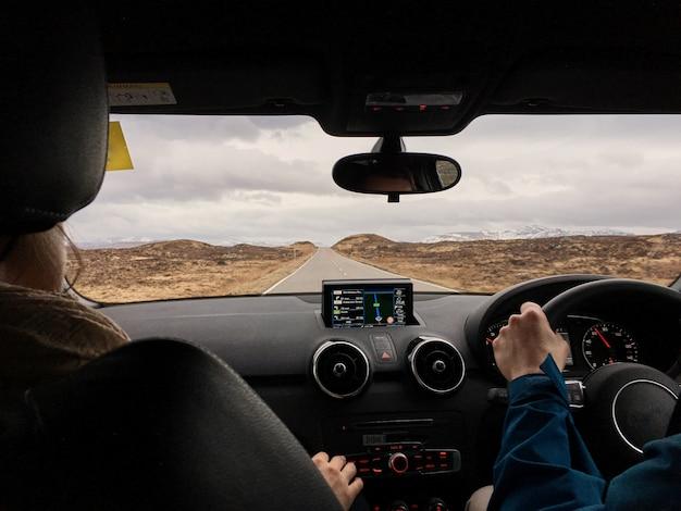 Widok z tyłu para siedzi na przednich siedzeniach i wyglądający przystojny mężczyzna jazdy samochodem