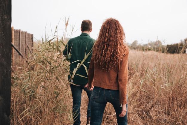 Widok z tyłu para spaceru przez pole pszenicy
