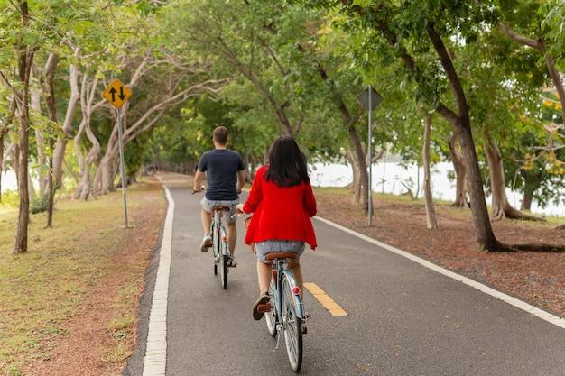 Widok z tyłu pary jeżdżącej na rowerach w parku