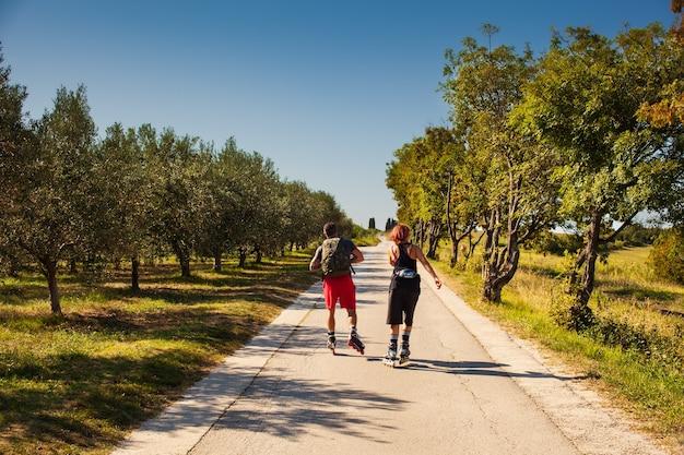 Widok z tyłu pary kochanków na łyżwach na rolkach na drodze obok oliwnego rowu