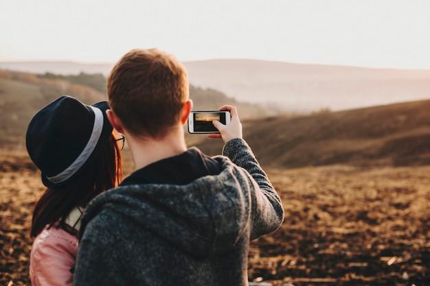 Widok z tyłu pary obejmującej się i robiącej zdjęcie na smartfonie przedstawiającej krajobraz o zachodzie słońca podczas podróży w czasie wakacji.
