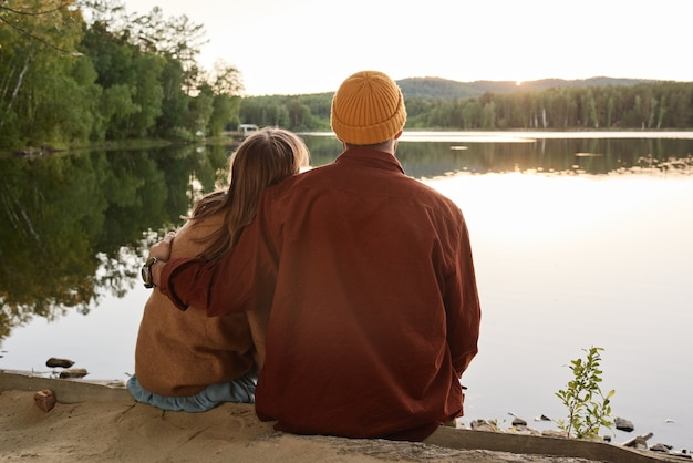 Widok z tyłu pary w ciepłej odzieży obejmującej się i cieszącej się pięknymi widokami na jezioro na zewnątrz