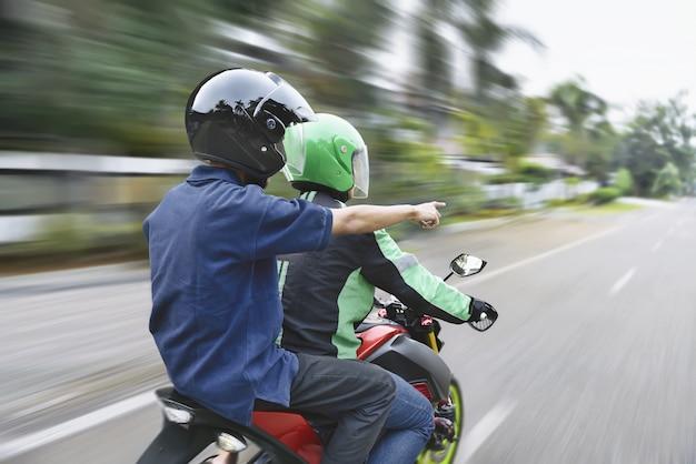 Widok z tyłu pasażera kierujący drogę do kierowcy taksówki motocykla