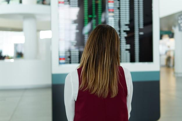 Widok z tyłu - piękna dziewczyna stoi i wybór lotu na tle niewyraźnej tablicy wyników z ogłoszeniem.