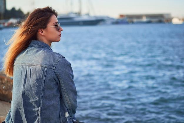 Widok z tyłu piękna kobieta w okularach przeciwsłonecznych siedzi i patrzy w prawo