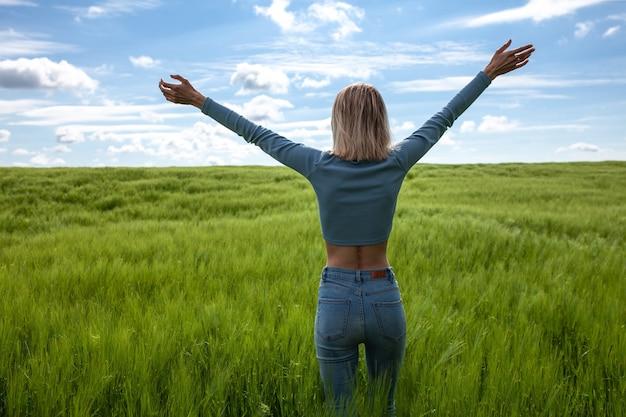 Widok z tyłu piękna młoda kobieta w dżinsach i niebieskim swetrze spaceruje po polu widok z tyłu kopia przestrzeń koncepcja wakacji letnich kobieta na plecach z wyciągniętymi ramionami