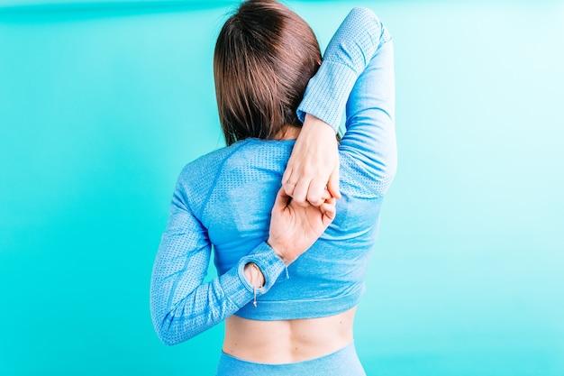 Widok z tyłu piękne dopasowanie młoda dorosła kobieta w rajstopach jogi patrząc rozciąganie ramion do tyłu. koncepcja zajęć jogi z miejscem na kopię