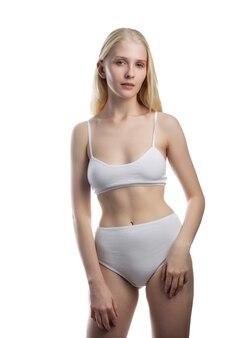 Widok z tyłu pięknej kaukaskiej kobiety w białym bikini, na białym tle.