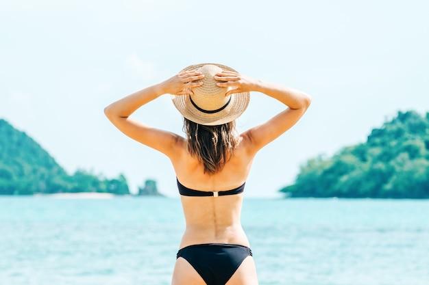 Widok z tyłu pięknej kobiety stwarzającej w czarnym stroju kąpielowym bikini i kapeluszu na wybrzeżu morza. koncepcja podróży i odpoczynku egzotyczny kraj