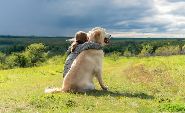 Widok z tyłu pięknej małej dziewczynki przytulającej lojalnego psa w przyrodzie
