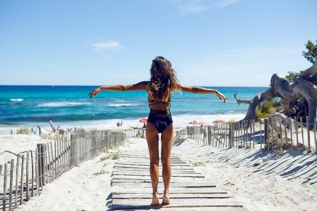 Widok z tyłu pięknej młodej kobiety pozowanie na plaży. ocean, plaża, piasek, tło nieba. wakacje na korsyce we francji.