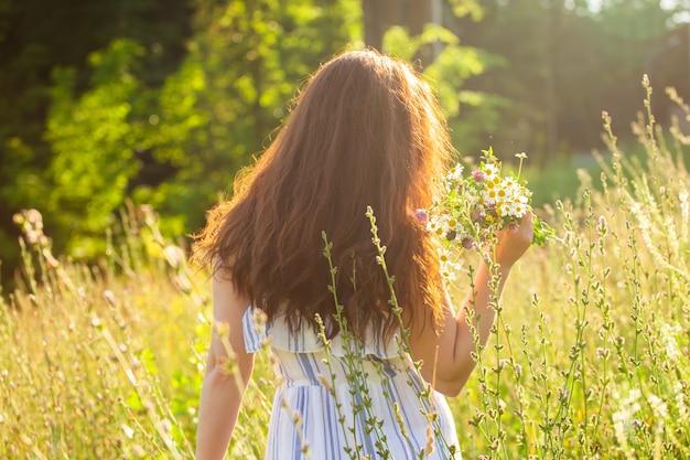 Widok z tyłu pięknej młodej kobiety spaceru wśród polnych kwiatów w słoneczny letni dzień