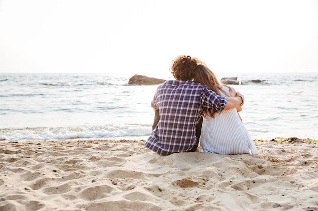 Widok z tyłu pięknej młodej pary siedzącej i przytulonej na plaży
