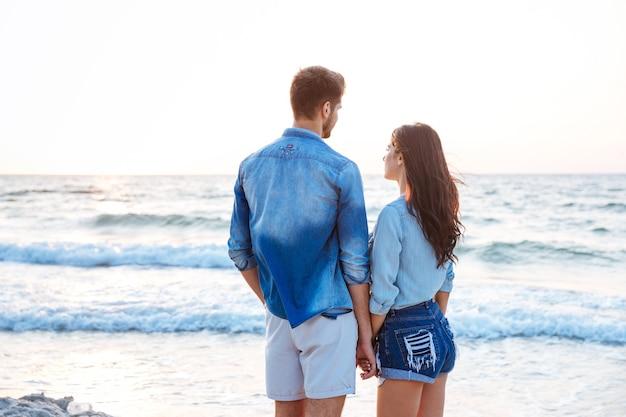 Widok z tyłu pięknej młodej pary trzymającej się za ręce na plaży