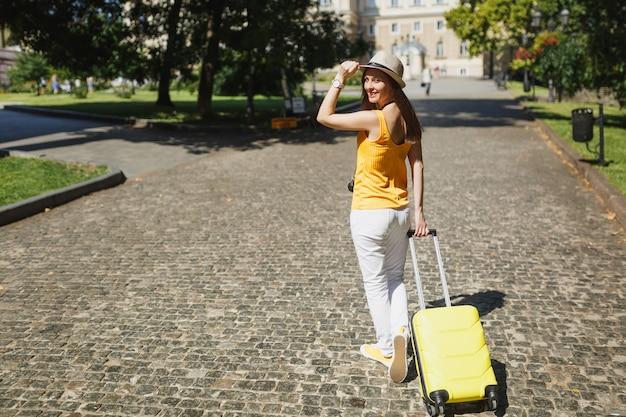 Widok z tyłu podróżnik turysta kobieta w ubranie trzymając rękę na kapeluszu z walizką rozglądając się po mieście na świeżym powietrzu. dziewczyna wyjeżdża za granicę na weekendowy wypad. styl życia podróży turystycznej.