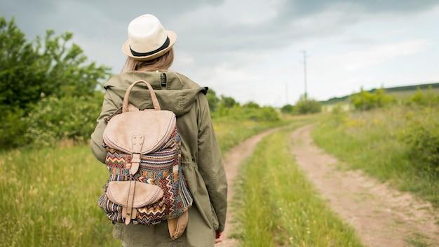Widok z tyłu podróżnik w kapeluszu, chodzenie na zewnątrz