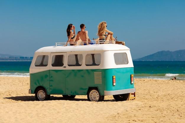 Widok z tyłu podróżnych cieszących się wakacjami na piaszczystej plaży