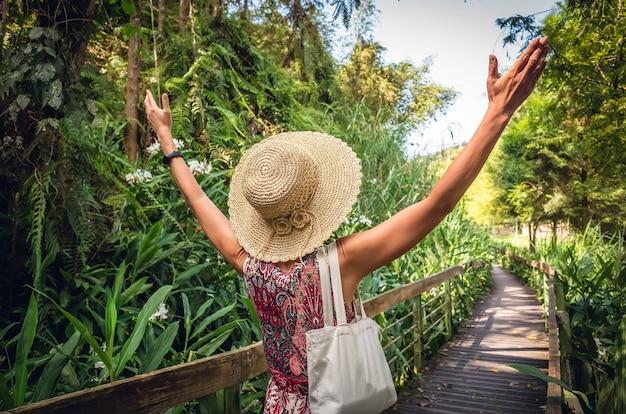 Widok z tyłu podróżującej azjatyckiej kobiety spacerującej po pasie w lesie
