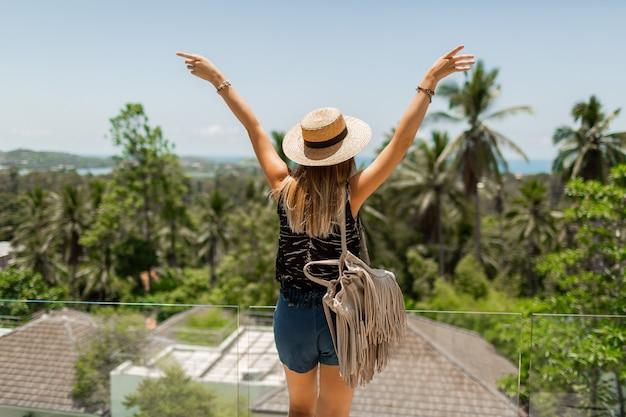 Widok z tyłu podróżującej kobiety w słomkowym kapeluszu, podziwiając niesamowity tropikalny krajobraz