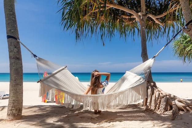 Widok z tyłu podróży kobiety siedzącej na białym hamaku na piaszczystej plaży