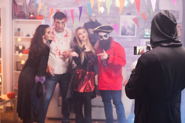 Widok z tyłu ponurego żniwiarza robienia zdjęcia przyjaciół na imprezie z okazji halloween.