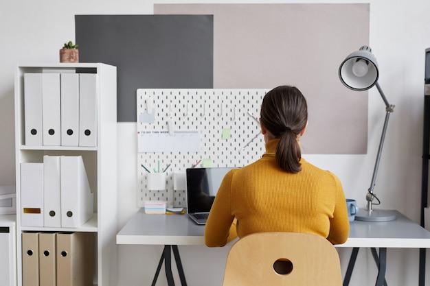 Widok z tyłu portret dorosłej kobiety za pomocą laptopa podczas pracy przy biurku w domu lub w biurze,