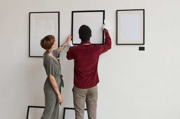 Widok z tyłu portret dwóch pracowników galerii sztuki wiszących na białej ścianie podczas planowania wystawy w muzeum,