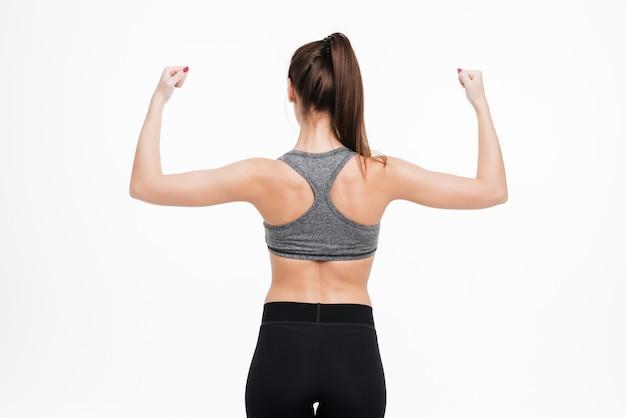 Widok z tyłu portret kobiety fitness pokazujący jej biceps na białym tle