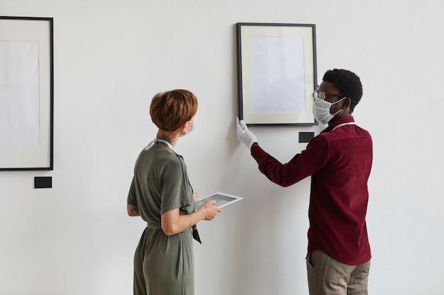 Widok z tyłu portret menedżerki w talii instruująca asystentkę noszącą maskę podczas planowania wystawy w galerii sztuki w muzeum,