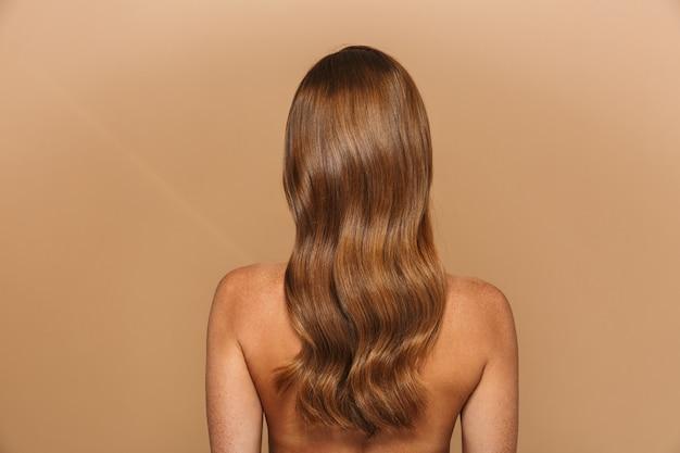 Widok z tyłu portret pięknej zdrowej młodej kobiety z długimi rudymi włosami na białym tle nad beżową ścianą