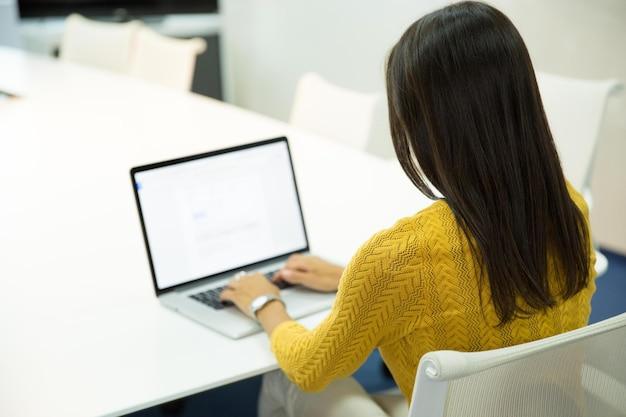 Widok z tyłu portret przypadkowej bizneswoman pracującej na laptopie w biurze