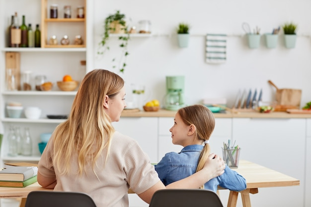 Widok z tyłu portret troskliwej matki przytulanie dziewczynki siedząc przy stole i pomagając jej uczyć się w domu, kopia przestrzeń