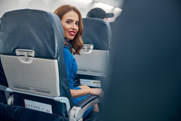 Widok z tyłu portret uroczej rudej kobiety siedzącej na wygodnym fotelu pasażera na pokładzie międzynarodowych linii lotniczych