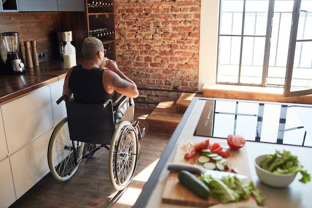 Widok z tyłu portret współczesnej wytatuowanej kobiety na wózku inwalidzkim, pijącej kawę w domu, kopia przestrzeń