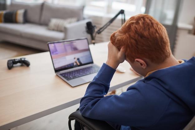 Widok z tyłu portret zmartwionego nastoletniego chłopca ponoszącego klęskę lub porażkę podczas grania w gry wideo, kopia przestrzeń