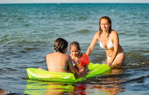 Widok z tyłu pozytywnej młodej rodzinnej mamy i dwóch małych córek pływających na żółtym materacu w morzu w słoneczny letni dzień podczas wakacji
