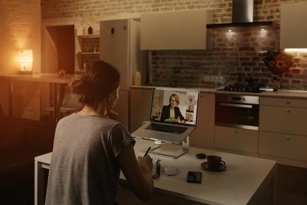 Widok z tyłu pracowniczki, która pracuje zdalnie i notuje przemówienie szefa podczas wideokonferencji na laptopie z domu.