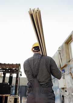 Widok z tyłu pracownika z kask niosący drewno