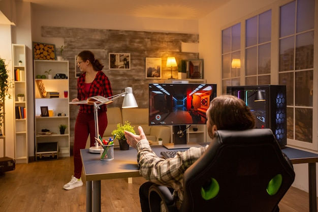 Widok z tyłu profesjonalnego gracza wideo grającego późną nocą na potężnym komputerze w salonie.